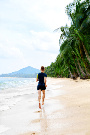 adult footprint: Fit Athlete Male Jogger Running On Beach.