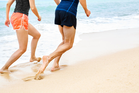 sport fitness: Closeup Of Athletic Runners Legs Running On Beach. Stock Photo