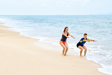 salud y deporte: Ejercicios de fitness. Pareja atlética Eyacular antes de ejecutar en la playa. Ajuste atlético hombre y mujer que ejercitan, haciendo sentadillas Antes de que activan en la costa. Deportes. Entrenamiento, estilo de vida saludable. Concepto de salud