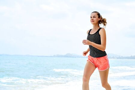 salud y deporte: Sports. Fit Female Athlete Jogger Running On Beach. Sporty Athletic Woman Jogging During Workout Outside. Fitness, Exercising, Healthy Lifestyle. Health Concept