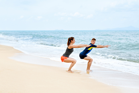 en cuclillas: Ejercicios de fitness. Pareja atlética Eyacular antes de ejecutar en la playa. Ajuste atlético hombre y mujer que ejercitan, haciendo sentadillas Antes de que activan en la costa. Deportes. Entrenamiento, estilo de vida saludable. Concepto de salud