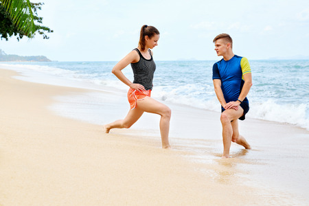 health and fitness: Athletics. Fit Athletic Couple Stretching Legs, Exercising, Preparing To Run. Athletes Warming Up, Doing Stretch Exercises Before Running On Beach. Sports, Fitness, Workout, Healthy Lifestyle Concept