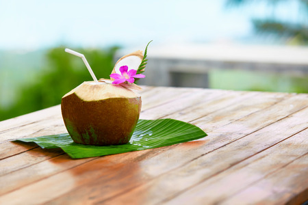 tropical drink: Diet Drink. Tropical Cocktail With Organic Raw Coconut Water Or Milk, With Drinking Straw And Orchid Flower. Nutrition And Hydratation. Detox Dieting. Vitamins. Healthy Lifestyle. Health Care Concept.
