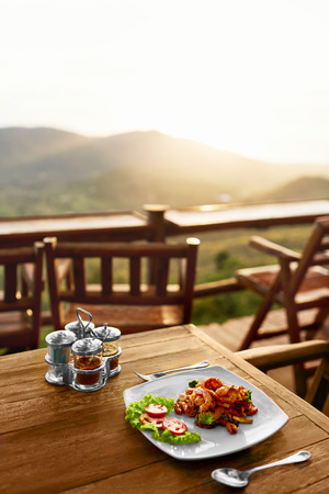 dish: Food. Dinner In Thai Restaurant Outdoors. Healthy Organic Meal On Wooden Table. Beautiful Landscape, View, Hills On Background. Travel To Luxury Tropical Resort. Thailand Vacations. Lifestyle.