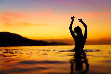 Freedom, Enjoyment. Silhouette Of Happy Free Young Woman Relaxing In Sea Water At Sunset. Summer Travel Holidays Vacation. Happiness, Beauty Nature. Healthy Lifestyle, Wellness , Body Care Concept.