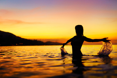 enjoyment: Freedom, Enjoyment. Silhouette Of Happy Free Young Woman Relaxing In Sea Water At Sunset. Summer Travel Holidays Vacation. Happiness, Beauty Nature. Healthy Lifestyle, Wellness , Body Care Concept.
