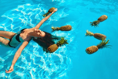 Beauty, Health Concept. Fresh Organic Fruits In Refreshing Pure Water. Beautiful Vegan Woman Relaxing ( Floating ) In Swimming Pool With Pineapples. Healthy Lifestyle, Nutrition, Diet. Summer Vacation