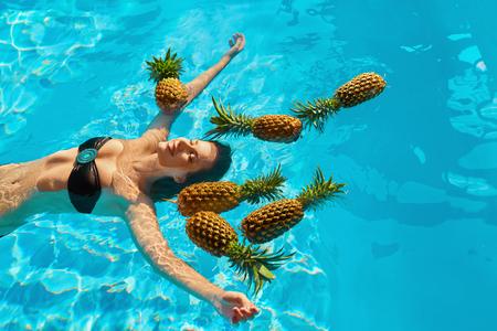 Alimentation saine, la nutrition. Concept de soins de santé. Sourire jeune femme de détente avec des produits frais Ananas bio En rafraîchissant l'eau pure dans la piscine. Fruits de la beauté. Mode de vie. Voyage Summer Vacation