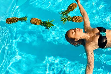 ヘルシー食品。幸せな美しいベジタリアン若い女純粋な水に浮かぶ新鮮な有機パイナップル付きのスイミング プールでリラックス。フルーツ、美容