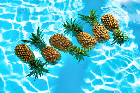 vegan food: Healthy Raw Organic Food. Fresh Ripe Pineapples Floating In Pure Water In Swimming Pool. Juicy Fruit. Vegetarian, Vegan Nutrition, Lifestyle. Eating Vitamins. Diet, Beauty, Health, Hydration Concept