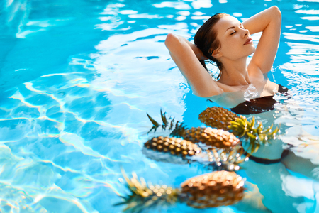 summer diet: Beauty, Health Concept. Fresh Organic Fruits In Water. Beautiful Young Woman Relaxing In Swimming Pool With Pineapples. Healthy Lifestyle, Nutrition, Body Care, Diet Background. Summer Vacation