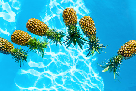 hydration: Juicy Fruit Background. Fresh Raw Organic Ripe Pineapples In Swimming Pool Water. Healthy Diet Food, Nutrition And Lifestyle. Eating Vitamins For Beauty, Health. Go Vegetarian. Hydration Concept.