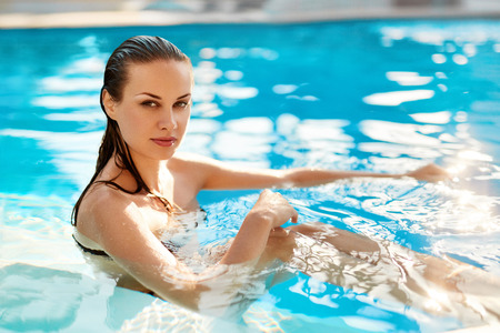 Body Care. Freshness Concept. Beautiful Sexy Young Woman Relaxing In Swimming Pool Water At Resort Spa Hotel. Health Care, Beauty Concept. Healthy Lifestyle, Wellness. Summer Travel Vacation.