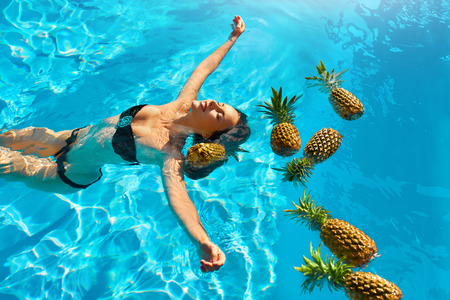 summer diet: Healthy Diet, Nutrition. Health Care Concept. Smiling Young Woman Relaxing With Fresh Organic Pineapples In Refreshing Pure Water In Swimming Pool. Fruits For Beauty. Lifestyle. Summer Travel Vacation