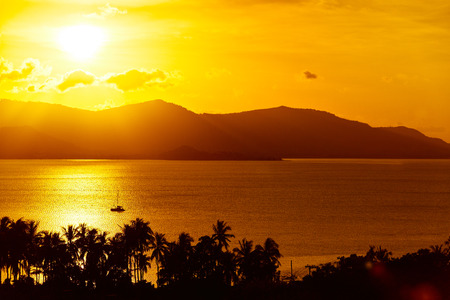 sea scenery: Nature Background. Scenic View Landscape Of Tropical Island Coast At Orange Sunset Over Beautiful Sea With Floating Boat And Palms Silhouette. Scenery. Travel To Thailand. Tourism. Summer Vacation