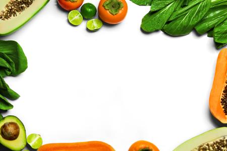 Essen Hintergrund. Gesunde Frische Rohe Bio-Obst und Gemüse. Bok Choy, Papaya, grüner Salat, orange Persimmon, Avocado, Kalk auf weißem Hintergrund. Vegetarische Ernährung. Ernährung und Vitamine Konzept