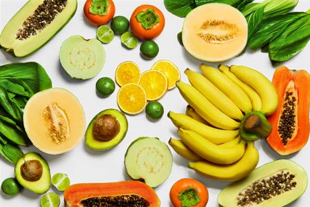 naranjas: Vehículos orgánicos saludables y frutas sobre fondo blanco. Frescos los alimentos crudos: Bok Choy, papaya, ensalada, caqui, aguacate, limón, plátano, melón, guayaba, naranjas. La nutrición vegetariana. La dieta y vitaminas Foto de archivo