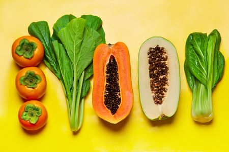 bok choy: Healthy Raw Organic Food. Close Up ?omposition Of Bok Choy, Green And Ripe Papaya, Persimmon, Green Salad Leaves. Fruits, Vegetables Background. Vegetarian Diet. Healthy Nutrition, Lifestyle. Vitamins Stock Photo