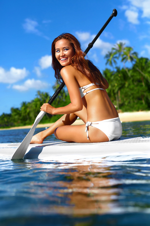 sporting activity: Water Sports. Beautiful Healthy Smiling Woman With Sexy Body In Bikini Paddling On Stand Up Paddle ( SUP, Surf ) Board In Ocean Near Beach. Hobby. Summer Travel Vacation. Leisure Sporting Activity.