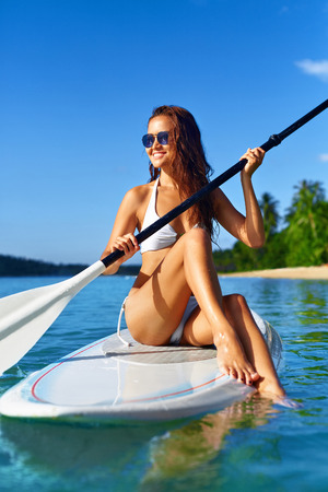 sexy asian woman: Recreational Sports. Healthy Happy Fit Woman With Sexy Body In Bikini Stand Up Paddle Boarding ( SUP, Surfing ) In Sea Water At Resort. Summer Fun, Holidays Travel Vacation. Active Lifestyle. Hobby Stock Photo
