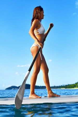 paddling: Summer Water Sports. Happy Fit Woman With Sexy Body Paddling, Standing Up On Paddle, Surf Board In Ocean. Holidays Travel Vacation. Healthy Active Lifestyle. Recreational Leisure Activity, Wellness. Stock Photo