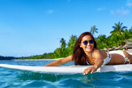 Summer Adventure. Water Sports. Happy Carefree Sexy Woman In Bikini Surfing, Lying On Paddle, Surf Board In Sea At Exotic Resort. Holidays Travel Vacation. Healthy Active Lifestyle. Leisure Activity. Фото со стока
