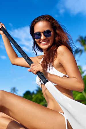 recreational sports: Recreational Sports. Healthy Happy Fit Woman With Sexy Body In Bikini Stand Up Paddle Boarding ( SUP, Surfing ) In Sea Water At Resort. Summer Fun, Holidays Travel Vacation. Active Lifestyle. Hobby Stock Photo