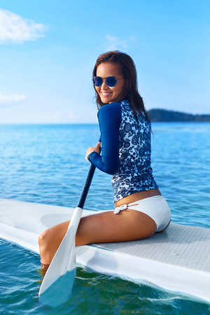 ocean water: Hobby. Healthy Happy Athletic Girl In Wetsuit Paddling On Stand Up Paddle ( SUP, Surfing ) Board In Ocean. Summer Fun, Holidays Travel Vacation. Lifestyle. Recreational Water Sports. Leisure Activity