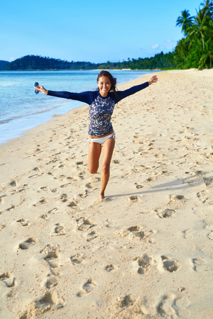 freedom leisure activity: Summer Fun On Holidays Travel Vacation. Healthy Happy Smiling Fit Woman Running On Beach At Exotic Resort. Lifestyle. Recreational Leisure Activity. Wellness, Happiness, Freedom, Enjoyment Concept