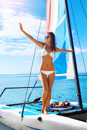 sporting activity: Summer Fun. Healthy Happy Woman With Sexy Fit Body In Bikini Enjoying Holidays Travel Vacation Standing On Small Sailing Catamaran At Exotic Beach Resort. Active Lifestyle. Leisure Sporting Activity