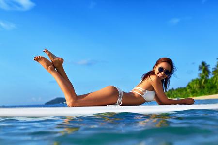 sonnenbaden: Urlaub Reisen. Sommer entspannen sich. Gesund Fit Frau mit sexy Körper in Bikini Sonnenbaden, relaxig Auf Surfen, Surfboard im Meerwasser. Exotische Resort. Freizeitsport. Schönheit, Wellness, Lifestyle. Lizenzfreie Bilder