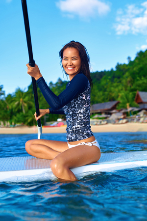 fun activity: Travel Adventure. Beautiful Fit Woman Paddling On ( SUP, Surfing ) Board In Sea At Resort. Recreation, Water Sports. Summer Fun, Holidays Vacation. Healthy Active Lifestyle. Leisure Activity. Wellness Stock Photo
