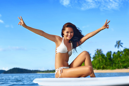 Summer Fun. Happy Young Surfer Woman With Sexy Fit Body In Fashion Bikini On Surfing, Surf Board In Sea Water Enjoying Travel Vacation In Tropical Resort. Sports, Healthy Lifestyle, Beauty, Wellness.