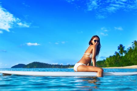 Viajes de vacaciones. Sexy hermosa mujer joven con el cuerpo en forma en el bikiní blanco se relaja en el Stand Up Paddle (Surf) tarjeta en el mar del agua en el centro turístico tropical. Concepto de estilo de vida saludable. Verano divertido. Deportes