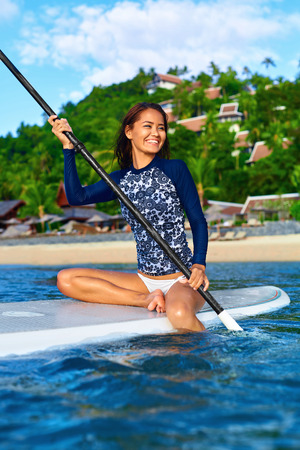 recreational sports: Hobby. Healthy Happy Athletic Girl In Wetsuit Paddling On Stand Up Paddle ( SUP, Surfing ) Board In Ocean. Summer Fun, Holidays Travel Vacation. Lifestyle. Recreational Water Sports. Leisure Activity