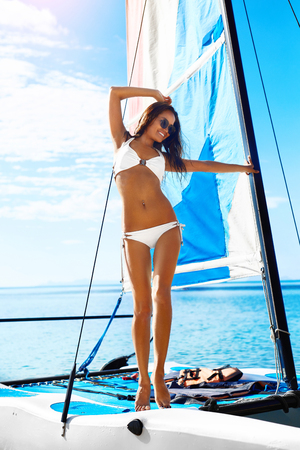 traje de baño: Verano divertido. Mujer sana feliz con ajuste atractivo cuerpo en bikini disfrutando de Vacaciones viajes de vacaciones Permanente En La Pequeña Vela Catamarán en exóticos Beach Resort. Estilo de vida activo. Ocio Actividad Deportiva Foto de archivo