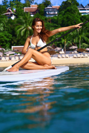 paddling: Water Sports. Beautiful Healthy Smiling Woman With Sexy Body In Bikini Paddling On Stand Up Paddle ( SUP, Surf ) Board In Ocean Near Beach. Hobby. Summer Travel Vacation. Leisure Sporting Activity.
