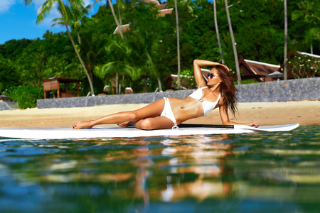 sunbathing: Vacation Travel. Summer Relax. Healthy Fit Woman With Sexy Body In Bikini Sunbathing, Relaxig On Surfing, Surf Board In Sea Water. Exotic Resort. Recreational Sports. Beauty, Wellness, Lifestyle.