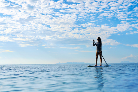paddling: Summer Water Sports. Silhouette Of Free Fit Woman Paddling, Stand Up On Paddle, Surf Board In Sea. Holidays Travel Vacation. Healthy Lifestyle. Recreation. Leisure Activity. Freedom, Wellness Concept