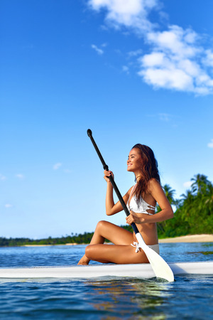 recreational sports: Leisure Sporting Activity. Happy Sexy Fit Woman In Bikini Stand Up Paddling ( SUP, Surfing ) On Surfboard In Sea Near Beach. Recreational Water Sports. Healthy Active Lifestyle. Summer Travel Vacation Stock Photo