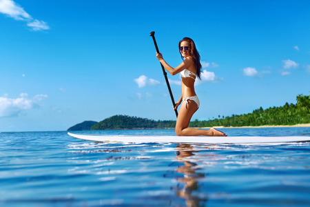 recreational sports: Recreational Water Sports. Healthy Happy Fit Woman With Sexy Body Paddling, Kneeling On Stand Up Paddle, Surf Board In Sea. Summer Holidays Travel Vacation. Active Lifestyle. Leisure Activity. Hobby Stock Photo
