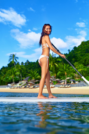 recreational sports: Summer Water Sports. Happy Fit Woman With Sexy Body Paddling, Standing Up On Paddle, Surf Board In Ocean. Holidays Travel Vacation. Healthy Active Lifestyle. Recreational Leisure Activity, Wellness. Stock Photo