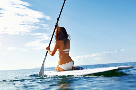 Leisure Sporting Activity. Happy Sexy Fit Woman In Bikini Stand Up Paddling ( SUP, Surfing ) On Surfboard In Sea Near Beach. Recreational Water Sports. Healthy Active Lifestyle. Summer Travel Vacation