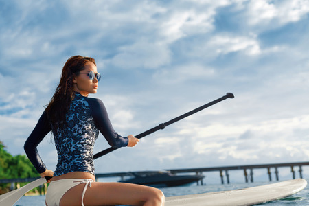 Travel Adventure. Beautiful Fit Woman Paddling On ( SUP, Surfing ) Board In Sea At Resort. Recreation, Water Sports. Summer Fun, Holidays Vacation. Healthy Active Lifestyle. Leisure Activity. Wellness 版權商用圖片