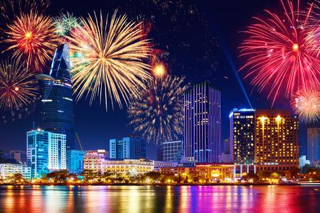 お祝い。ホーチミン市 (サイゴン)、ベトナム ビジネス地区上空を花火とスカイライン。夜景ビュー街並み、都市景観。新しい年を祝う休日。