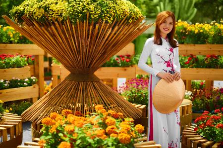 Kultur Asiens. Schöne glücklich lächelnde junge asiatische Frau tragen traditionelle weiße Ao Dai-Kleid (Kleidung), Vietnamesisch Konische Hat (Non La) Blatthut Im Blumengarten in Ho-Chi-Minh-Stadt, Vietnam