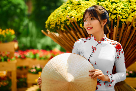 Culture Of Asia. Beautiful Happy Smiling Young Asian Woman Wearing Traditional White Ao Dai Dress ( Clothing ), Vietnamese Conical Hat ( Non La ) Leaf Hat In Flower Garden In Ho Chi Minh City, Vietnam