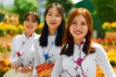 vietnam culture: Asian People. Beautiful Happy Smiling Women ( Girls, Friends ) Wearing National Traditional Ao Dai Dresses ( Vietnamese Costume, Clothing ) In Flower Garden, Ho Chi Minh City, Vietnam. Culture Of Asia Stock Photo