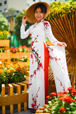 ao: Culture Of Asia. Beautiful Happy Smiling Young Asian Woman Wearing Traditional White Ao Dai Dress ( Clothing ), Vietnamese Conical Hat ( Non La ) Leaf Hat In Flower Garden In Ho Chi Minh City, Vietnam Stock Photo