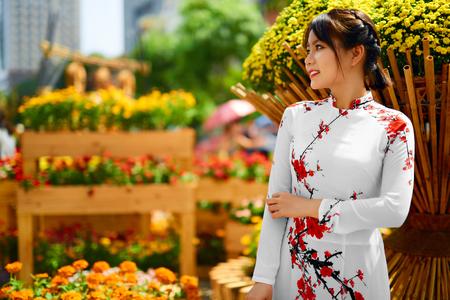 ao: Asian Beauty Woman. Beautiful Happy Vietnamese Girl Wearing National Traditional White Ao Dai Dress ( Clothing, Costume), Standing In Flower Garden, Ho Chi Minh City, Vietnam. Culture Of Asia